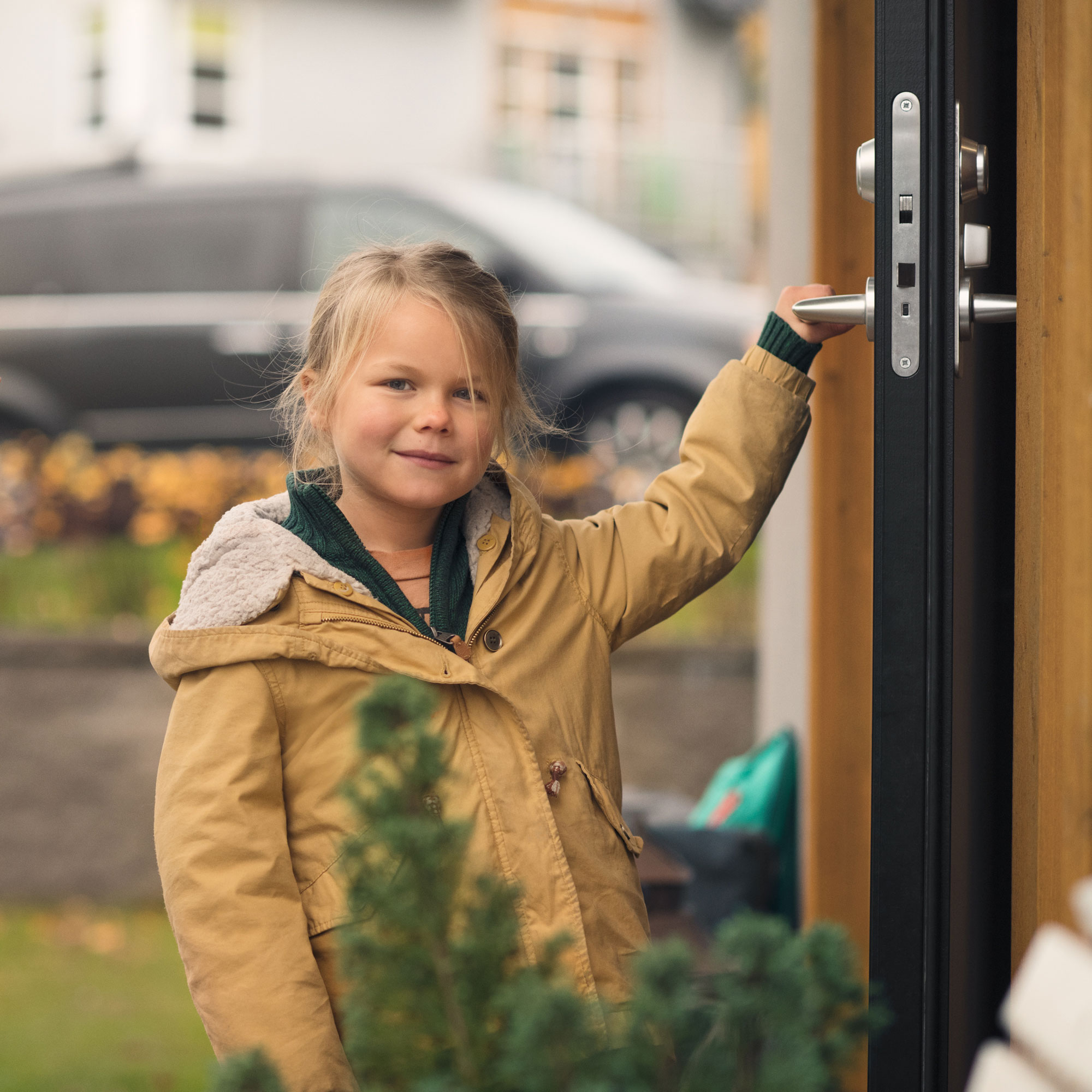 Young boy opening the front door to his house