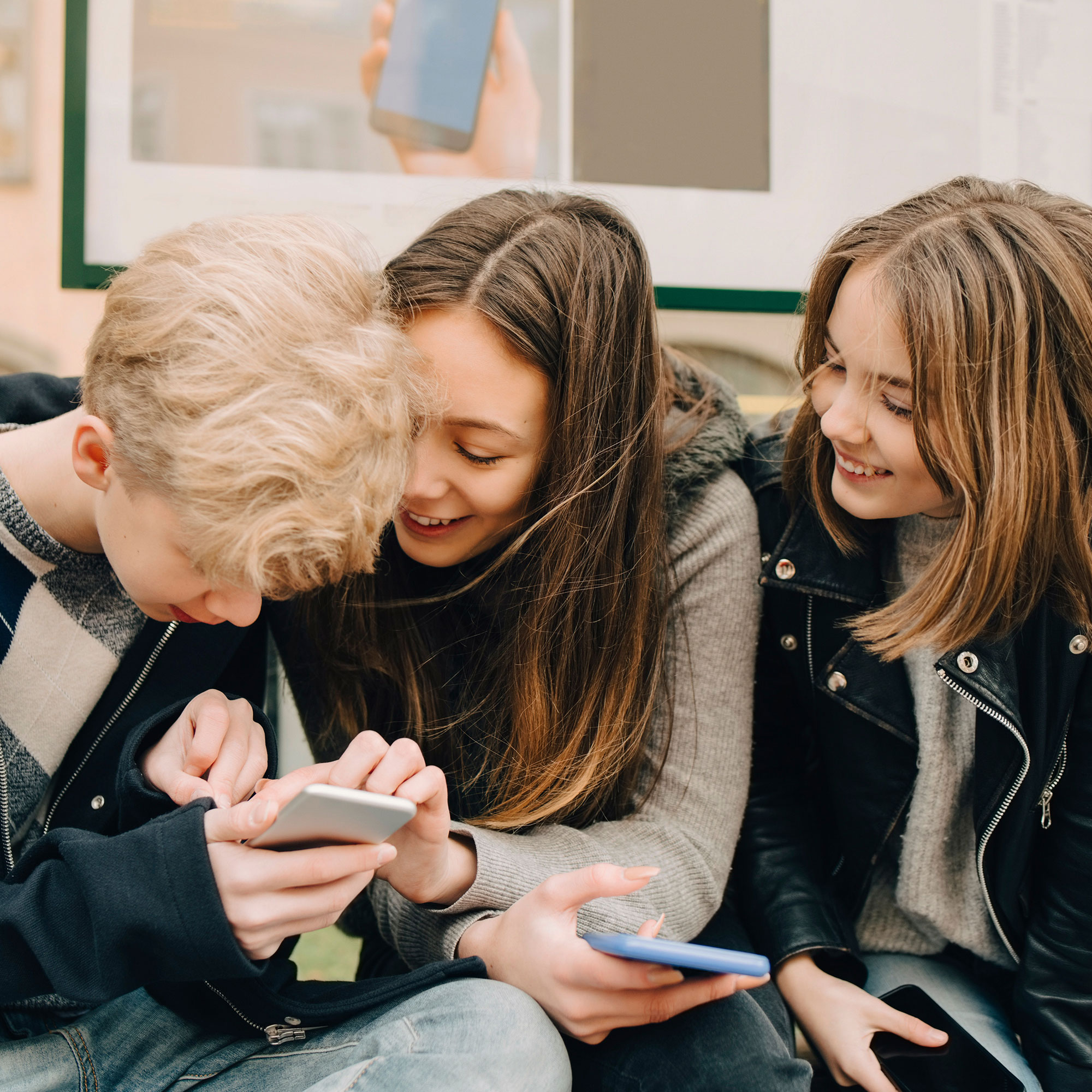 Youths at a bus stop looking at mobile.