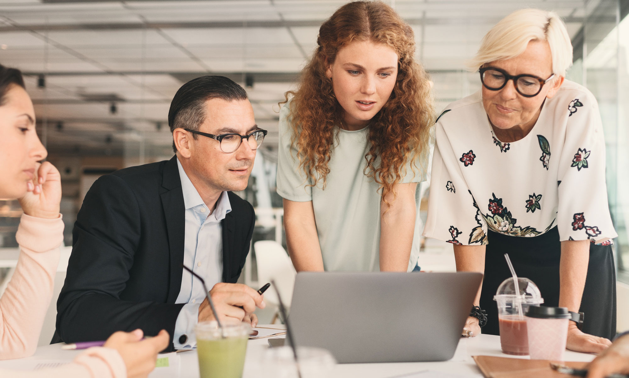 Business people looking at chart on a laptop.